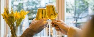 Personas brindando con copas de cerveza